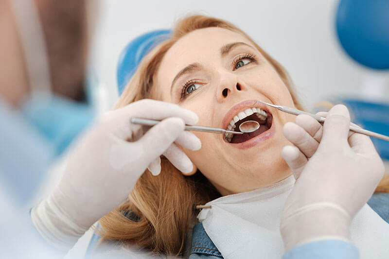 Middle-aged woman getting her teeth examined